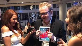 NOEL QUALTER entertains two women with iPad magic at a Christmas party