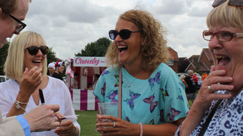 NOEL QUALTER makes three women laugh with iPad magic at a large outdoor event